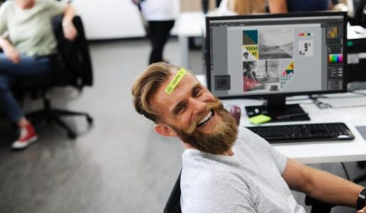Man at desk smiling as he is happy in his work environment