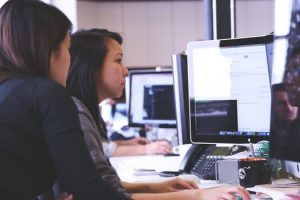 Two women working at a computer in a clean work environment