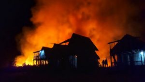 Fire Restoration Services look on as a terrible fire engulfs a beautiful house.